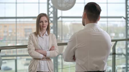 talk : Attractive blonde businesswoman with crossed arms speaking with man standing back to the camera Stock Footage