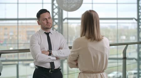 dialog : Businessman and businesswoman standing in the hall of modern office building with crossed arms and talking about something