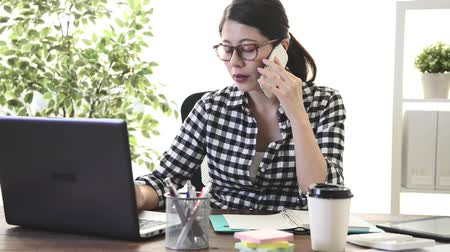 bizneswoman : young beautiful female company manager using computer and smartphone calling writing  for client discussing cooperation case. Wideo
