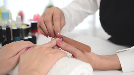 tampon : happy concentrate manicurist doing nail rub by using shiner file tool for her client. real salon spa background. beauty and fashion concept.