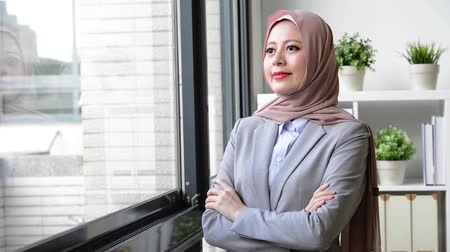 ислам : young professional muslim business woman standing in front of window and looking at outside thinking work plan.