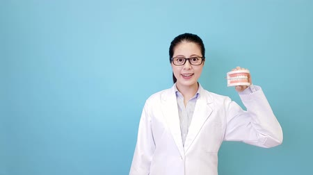 smiling elegant female hospital dentist showing dental teeth mold and making presentation posture and walk into isolated blue background. Wideo