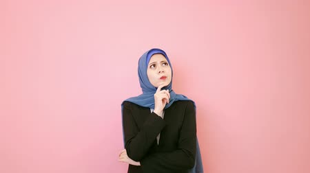 ислам : young muslim female company leader encountered difficulty problem feeling unhappy and standing in pink background thinking solution. Стоковые видеозаписи
