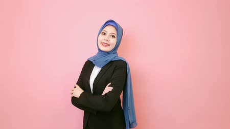 muslim leader : professional pretty muslim business woman standing in pink wall background face to camera and hands crossed put on chest.