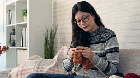 chunky : pretty asian woman sitting on sofa looking autumn outside of window and making seasonal knitting for winter coming and in the living room at home