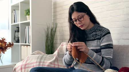 вязание : charming Asian woman sitting on the sofa looking outside of the window and making seasonal knitting for winter coming and in the living room at home in the autumn season