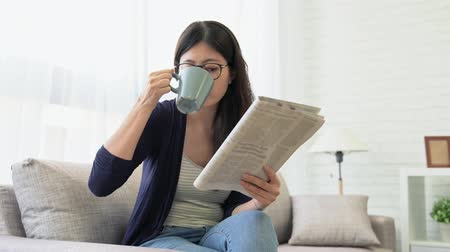 японский : Dolly shot of attractive happy woman reading newspaper and holding hot coffee mug sitting in front of window comfortable sofa at home. Стоковые видеозаписи