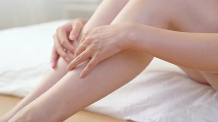 haj : hair removal concept. young girls hand With natural manicure touching long leg smoothly up.