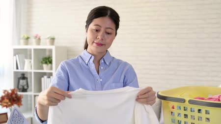 verifying : beautiful young lady pick up the white clothes in the laundry basket make sure the white clothes are clean. housewife feel satisfied in living room . Stock Footage