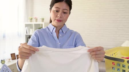 verifying : pretty smiling housekeeper woman inspecting white clothes checking whether clean. housewife satisfied with the washing result
