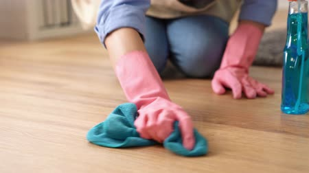 galo : Woman uses cleaner and rag to work hard to wipe the floor back and forth for end of year cleaning housewife scrub floor at home