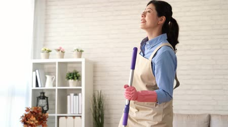 amalucado : Tilt shot of asian female cleaning woman having fun during spring cleaning. Funny woman cleaning wearing rubber gloves singing in the living room at home. housework and household idea concept. Stock Footage