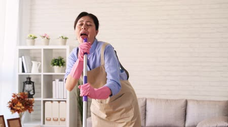 kötény : Beautiful young woman in protective gloves is singing using a mop and dancing while cleaning her house in living room during end of year clean