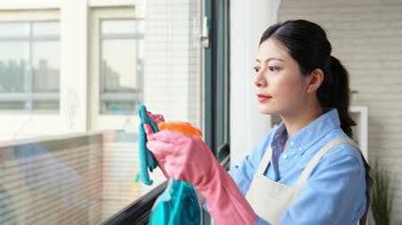 cleaning products : Spring cleaning woman clean window with rubber gloves rag and detergent during daily clean at home