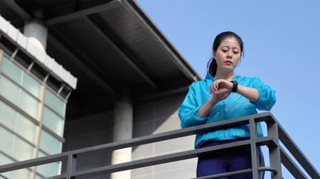 atlet : asian girl running in the modern city. Female runner looking at her sport watch check and measuring heart rate