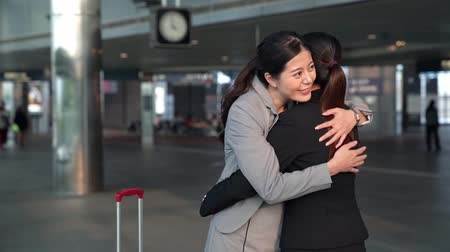 sarılmak : slow motion movement of happy businesswoman meeting her best business friend in the train station and hug together.