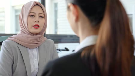 muslim leader : hijab Muslim woman manager looking at business partner during a conversation.