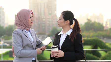muslim leader : Quick briefing before meeting. two cheerful young business people talking to each other while walking outdoors Stock Footage