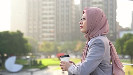 malajské : successful Muslim businesswoman standing outside of office take a break enjoy coffee and looking far away vision.
