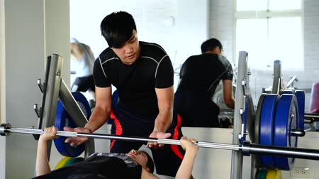 safe workout : Asian strong male coach helps the female students to lift the dumbbells slowly in the gym.