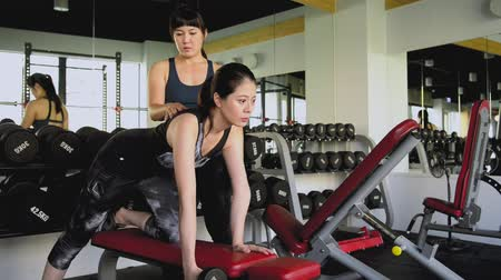 safe workout : Female Asian coach teaches the girl. She teaches the girl how to build up the muscle in a fierce way.
