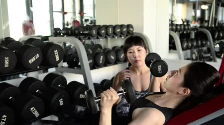safe workout : Asian slim girl lifts up the dumbbells without anyones help. She lifts it up steadily.