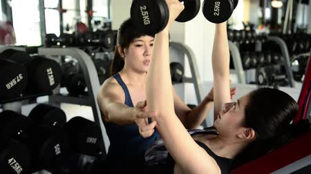 safe workout : Female strong coach aware of the safety of the girl while she lifts up the dumbbells. Stock Footage