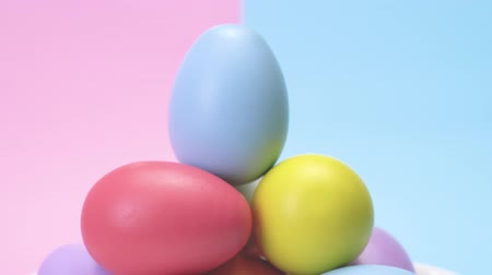 easter : A heap of coloured eggs rotating and the blue one is on the top. On a punchy pastel background.