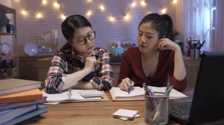 Young asian college women stay up late sitting at wooden table in night dining room at home.