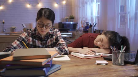Young hard working girl student reading book while friend is sleeping on desk. Wideo