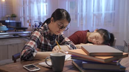 young asian college girl student in glasses sitting at desk with books near tired friend. Wideo
