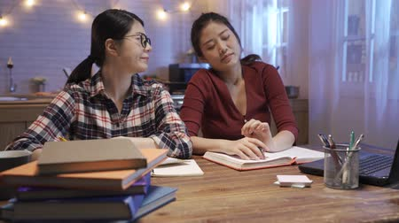 Kind college student waking up tired friend to get back study for exam. young girl in glasses doing homework and waking up her roommate to continue learning. two ladies hard working in night kitchen.
