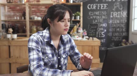 Thoughtful young asian businesswoman work on laptop in cafe bar. Pensive attractive woman freelancer thinks over the solution of problem looking at computer screen. female barista busy in coffee shop Dostupné videozáznamy