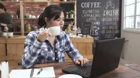 millennial asian female student searching online information on laptop computer in cafe preparing for test. young woman studying and drinking hot tea in coffee house. college girl typing on keyboard.