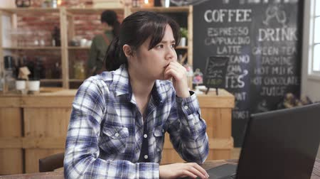 Confused asian woman freelance worker work on computer in cafe store with troubles on project. frowning female pensive thinking how to solve problem in coffee shop using laptop. waitress in counter
