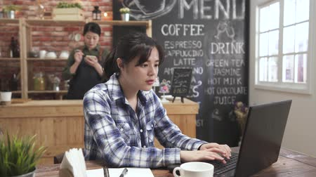 Experienced female barman making cappuccino in blurred background. elegant asian korean woman using laptop while sitting at cafe bar. Young college girl in coffee shop studying and prepare exam.