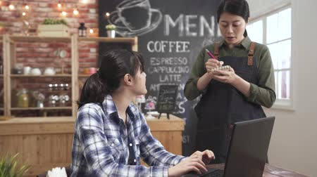 Content friendly asian japanese waitress in apron holding notebook for work and asking woman guest about food and drink preferences. businesswoman working in cafe and taking order to female bartender