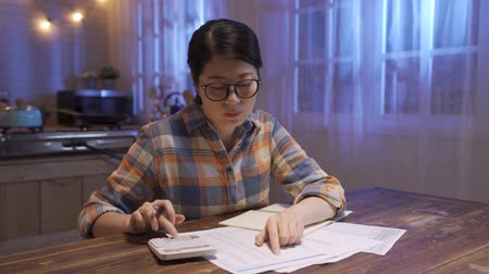 savings finances economy and home concept. worried young asian chinese woman with calculator counting money and making notes at night apartment. upset mom in glasses work on family financial late.