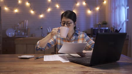 Smiling young asian chinese woman working in home kitchen at night using laptop and documents. elegant office lady stay up late doing work and drinking coffee to keep away in midnight in house. Dostupné videozáznamy