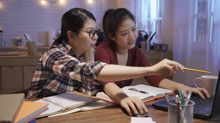 asian japanese university student girls working in night kitchen at home. young women friends discussing on laptop computer together during prepare presentation project. two roommates at dining table