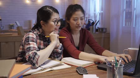 fast forward two asian girl students studying in night home kitchen. Young female people spending time hard working together on laptop pc. women team work partner smiling and discussing on notebook.