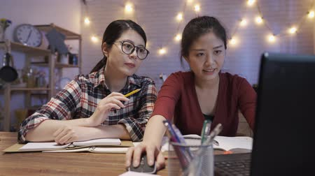 female college students using laptop while sitting at dining table. Group of girl partners study for school assignment. two ladies talking and discussing on notebook pc in night kitchen at home.