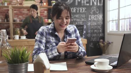 Happy young woman sitting in coffee shop texting on her smart phone. bokeh view of asian female waitress standing in bar counter preparing customer meal. charming lady smiling while using cellphone.