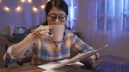 pretty young asian japanese woman studying while sitting at wooden table with laptop computer and notebook at home kitchen in late night. college girl drinking cup of tea to keep awake in midnight.