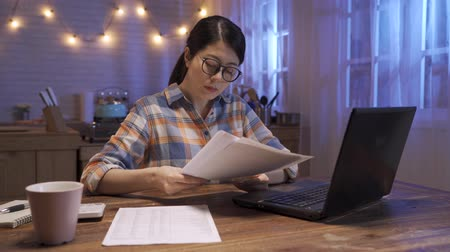 носить : Young beautiful woman working on laptop computer and documents at night. lady in home office in late midnight reading paperwork. elegant asian chinese female wear glasses sit in dark kitchen Стоковые видеозаписи