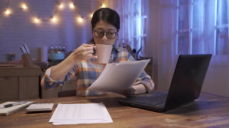 Attractive young asian korean woman in glasses working on laptop at night kitchen. elegant girl worker using notebook computer and document paper. female businesswoman in midnight drinking coffee.