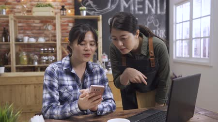 female barista chatting with girl guest in cafe store. asian chinese woman customer sitting at wooden table with laptop and showing waitress cellphone screen. Occupation people and service concept. Dostupné videozáznamy