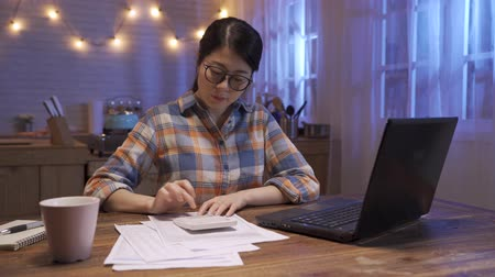 business deadline and people concept. young beautiful asian businesswoman with laptop computer and papers working at night home kitchen. lady stay up late counting finance on calculator of company Wideo
