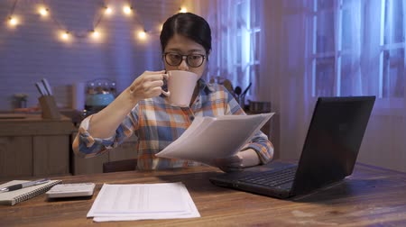 fast forward of young pretty woman worker working on laptop computer with paper at night in dark home kitchen. female designer stay up late. office lady overwork counting on calculator drinking tea