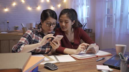 Cheerful friends viewing funny photos in social networks via smartphone together at kitchen table in dark night. happy female students relax in break time from studying and using mobile phone Wideo